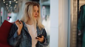 Het glimlachende blondemeisje leest iets in haar telefoon die met het winkelen zakken rond een winkelcomplex lopen stock video