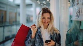 Het glimlachende blondemeisje typt iets in haar telefoon die met het winkelen zakken rond een winkelcomplex lopen stock videobeelden