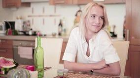 Het glimlachende blondemeisje zit bij lijst in keuken wanneer de jonge mens van haar bedrijf lid wordt stock videobeelden