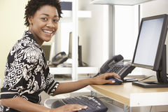 Het glimlachende Bureau van Onderneemsterusing computer in Stock Foto's