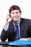 Het glimlachende Bureau van Zakenmanusing phone in royalty-vrije stock afbeelding