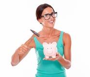 Het glimlachende donkerbruine spaarvarken van de vrouwenholding Stock Foto