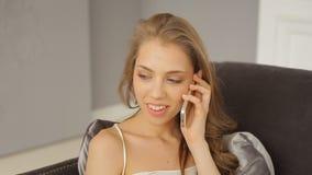 Het glimlachende elegante meisje draait en spreekt elegant op telefoon stock footage