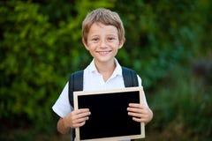 Het glimlachende Gelukkige Kaukasische Lege die Schoolbord van de Jongensholding op Wit wordt geïsoleerd stock afbeeldingen