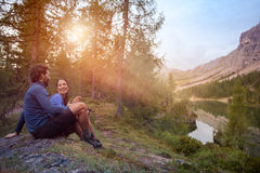 Het glimlachende gelukkige man en vrouwenpaar geniet van de mening van het meerpanorama met het licht van de zongloed Groep de zo stock foto's