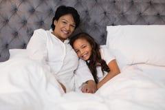 Het glimlachende grootmoeder en kleindochter ontspannen op bed thuis stock foto's