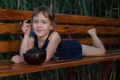 Het glimlachende ittle meisje ligt op een houten bank met een bes in haar hand royalty-vrije stock foto's