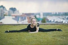 Het glimlachende jonge meisje op het groene gras voert streng, op achtergrondcityscape uit stock foto