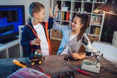 Het glimlachende jongen en meisjesconcepten technische stuk speelgoed en maakt robot Technisch stuk speelgoed op lijsthoogtepunt  royalty-vrije stock foto's
