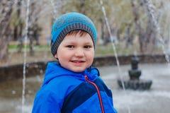 Het glimlachende kind bevindt zich op de achtergrond van de fontein en bekijkt de camera royalty-vrije stock afbeeldingen