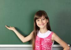 Het glimlachende kindmeisje houdt zijn hand dichtbij leeg schoolbord, royalty-vrije stock foto