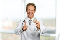 Het glimlachende medicijn van de artsenholding stock foto's
