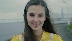 Het glimlachende meisje bevindt zich op een pijler met een brug op de achtergrond in slo-mo stock footage