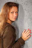 Het glimlachende meisje dat gebreide blouse draagt klampt zich aan muur vast Stock Foto's