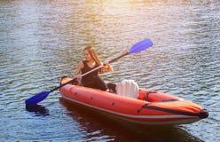 Het glimlachende meisje - de sportvrouw met lang, donker haar in zwarte, sportkledingsrijen met een roeispaan op het meer in een  Stock Fotografie