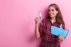 Het glimlachende meisje die een document tandenborstel houden en duimen ondertekent omhoog en aan de kant kijken Op een roze acht royalty-vrije stock afbeelding