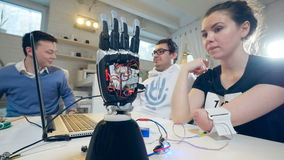 Het glimlachende meisje draait haar geamputeerde hand rond en de robothand opent gelijktijdig zijn palm stock footage
