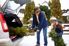 Het glimlachende meisje en de vader krijgen Kerstmisboom in openlucht uit autoboomstam dichtbij hun huis De dochter helpt papa me royalty-vrije stock fotografie