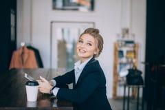 Het glimlachende meisje in firmal clothers heeft tot pizza opdracht gegeven stock afbeeldingen