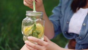 Het glimlachende meisje in hoed geniet van een gekoelde limonade op aard stock videobeelden