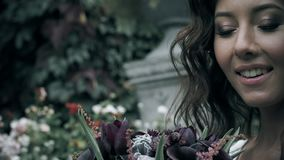 Het glimlachende meisje kijkt en raakt een boeket van bloemen stock videobeelden