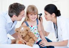 Het glimlachende meisje kijkt gelukkig met haar teddybeer Royalty-vrije Stock Foto's