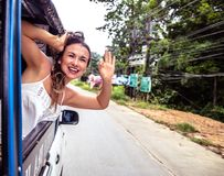 Het glimlachende meisje kijkt uit het venster van een taxi, tuk-Tuk Royalty-vrije Stock Foto's