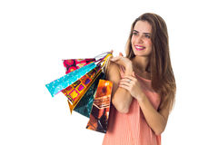 Het glimlachende meisje kijkt weg en hief in de handen van mooie heldere pakketten op Stock Foto's