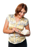Het glimlachende meisje leest datebook stock afbeeldingen