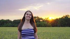 Het glimlachende meisje loopt door het de tarwegebied en draaien bij zonsondergang stock footage