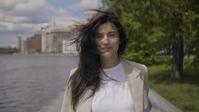 Het glimlachende meisje loopt langs de rivier stock video