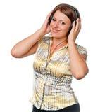 Het glimlachende meisje luistert aan muziek in oortelefoons stock fotografie