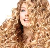 Het glimlachende meisje met blonde permed haar Stock Foto