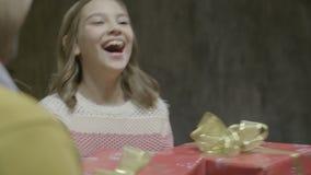 Het glimlachende Meisje neemt de Doos van Familiekerstmis van Ouders stock footage
