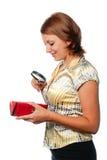 Het glimlachende meisje overweegt een beurs door meer magnifier stock afbeelding