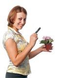Het glimlachende meisje overweegt viooltjes door meer magnifier royalty-vrije stock fotografie