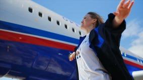 Het glimlachende meisje steekt handen tegen vliegtuig en hemel op stock video