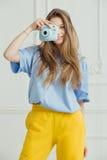Het glimlachende meisje in toevallige doek maakt foto door draagbare camera Stock Afbeeldingen