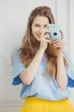 Het glimlachende meisje in toevallige doek maakt foto door draagbare camera Stock Fotografie