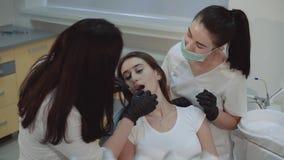 Het glimlachende meisje zit in tandkabinet bij behandeling en het consultating stock footage