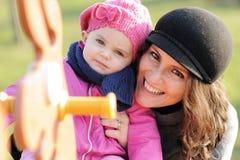 Het glimlachende moeder en kind spelen op de schommeling Royalty-vrije Stock Afbeelding