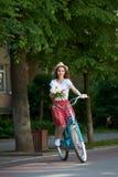 Het glimlachende mooie meisje in rode rok die blauwe die fiets berijden bedekte neer stadsstraat met groene bomen wordt omringd stock foto's