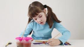 Het glimlachende mooie meisje schildert waterverfvlinder op lijst stock videobeelden