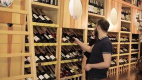 Het glimlachende paar die samen fles wijn in wijnhuizen kiezen, een jong paar kiest wijn op een wijnplank in een opslag stock video