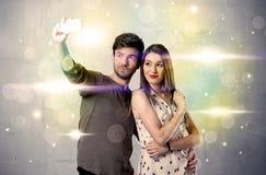 Het glimlachende paar die selfie schittert binnen licht nemen Royalty-vrije Stock Afbeeldingen