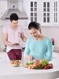 Het glimlachende paar eet salade in de keuken royalty-vrije stock foto