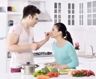Het glimlachende paar eet salade in de keuken stock foto