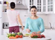 Het glimlachende paar eet salade in de keuken stock afbeeldingen