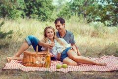Het glimlachende paar heeft rust in hout op picknick Stock Afbeeldingen