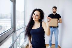 Het glimlachende paar pakt dozen in nieuw huis uit Stock Foto's